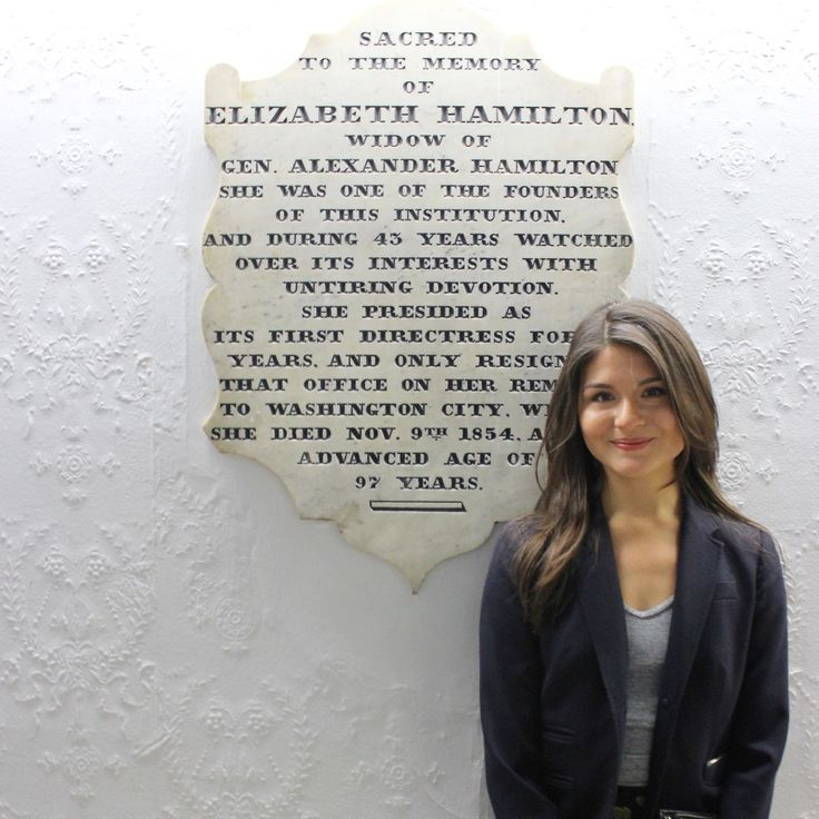 "Philippa Soo, who plays Eliza Schuyler Hamilton in ""Hamilton,"" stands in front of a plaque at the still-operational orphanage that the real ELiza Hamilton founded. [How the Cast of 'Hamilton' Made Philanthropy Their Mission]"