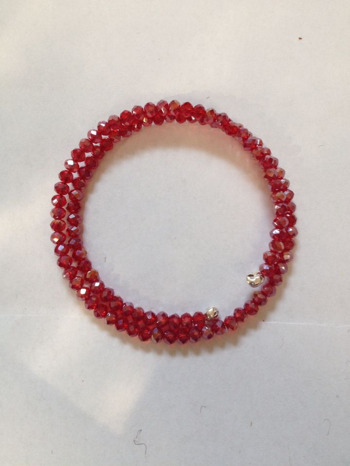 Braccialetto con filo armonico e cristalli rossi.  Memory wire and red crystals bracelet.