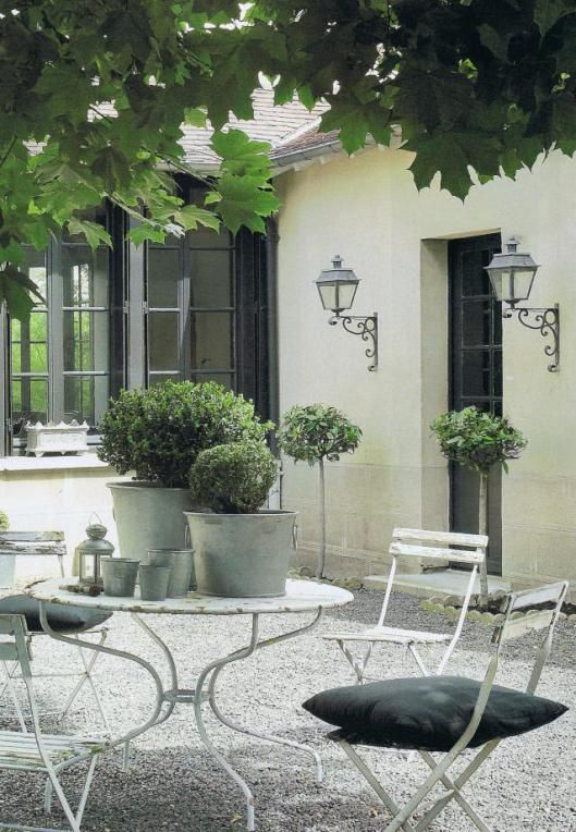 Classic Courtyard with French bistro style white garden furniture and simple clean styling. Elegant
