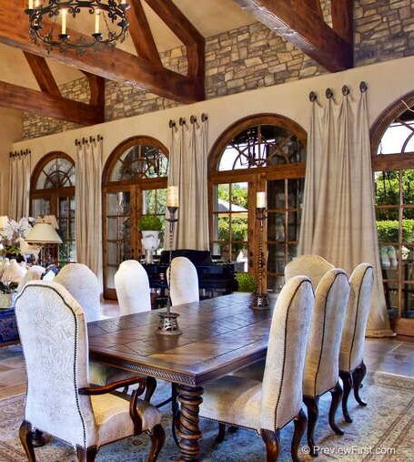 Old-world style morning room with arched windows and wood beam trusses.