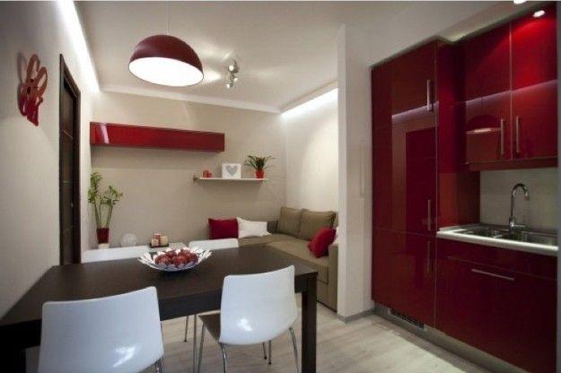 La cucina ha tavolo, sedie, frigorifero, lavandino, divano, armadi, porta, fioriere e decorazione.