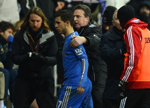 Chelsea's Belgium midfielder Eden Hazard (C) is escorted off the pitch after being sent off by referee Chris Foy (C) after an incident involving a ball boy during the English League Cup semi-final second leg football match between Swansea City and Chelsea at The Liberty stadium in Cardiff, south Wales on January 23, 2013