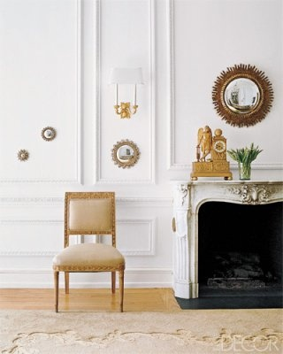 A constellation of mirrors by Line Vautrin hangs in the dining room of a 1902 townhouse in Manhattan decorated by Lee Mindel. Floating playfully between the moldings, the starburst frames lend whimsical glamour to the formal space, which also features a gilded chair and mantel clock.