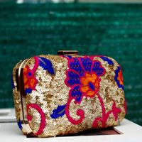 A gold clutch with colorful floral embroidery by Pookaari, a Weddingsutra Favorite. #WeddingSutra #weddingaccessories #wedding #accessories #ideas #indianwedding #Indian #designs #clutch #gold #sequence #floral