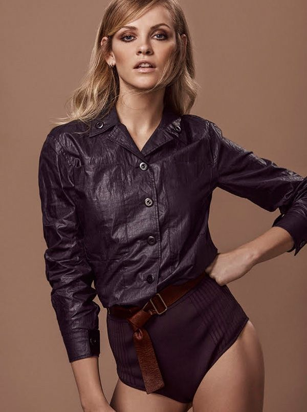 The model poses in crinkled shirt with belted briefs