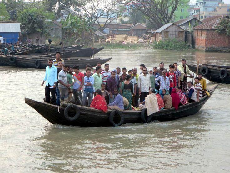 Heavily loaded passenger boats cross the Rupsa River at Khulna, Bangladesh.
