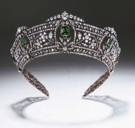 A MAGNIFICENT ANTIQUE EMERALD AND DIAMOND TIARA   Comprising seven graduated step-cut emeralds set within sprays of diamond flowerheads and leaves, running between borders of continuous diamond collets and ribbon motifs, mounted in silver and gold, circa 1900