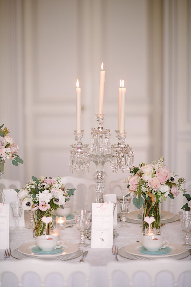 The inspirational wedding reception table featured crystal candelabra centerpieces bordered by white and pink bouquets and surrounded by taper candles. #candelabra #centerpiece #candles Photography: Milton Photography. Read More: http://www.insideweddings.com/weddings/inspirational-pastel-wedding-at-a-french-chateau-in-paris-france/650/