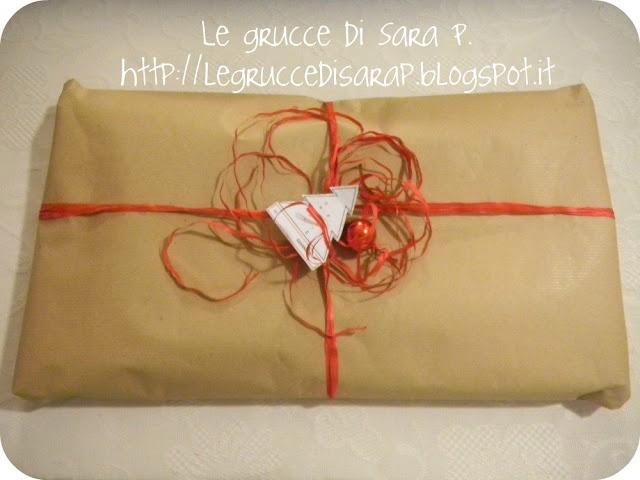 Pacco regalo con nastro di rafia rosso e pallina di Natale