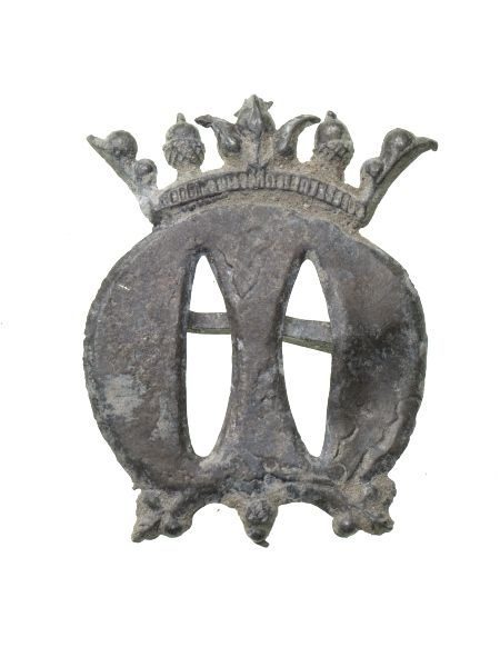Pilgrim badge of the Virgin Mary from an unknown shrine. This badge depicts a crowned letter 'M', which stood for Maria, Queen of Heaven. The crown is decorated with two acorns. The Virgin was thought of as a universal protector.  Production Date: Late Medieval; 15th century