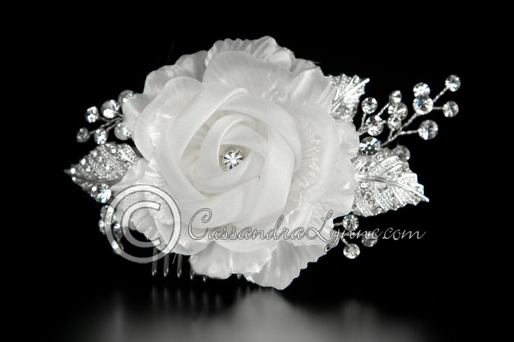 This white chiffon bridal hair flower is surrounded by stunning textured leaves with a few jewels and rhinestone sprays. On a silver metal comb it is about 4.5 inches long and 2.5 inches wide.