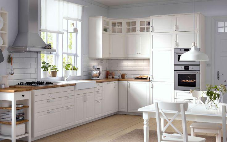 Cucina tradizionale con mobili bianchi, piani di lavoro in legno, ante a vetro ed elettrodomestici integrati