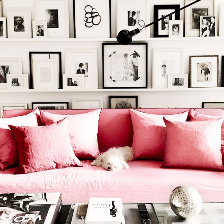 Pink sofa in white and black living room with big gallery wall