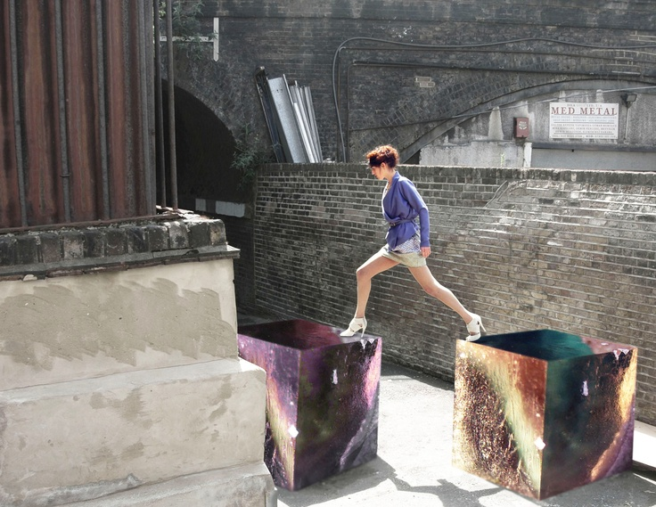 A model wears the DIYcouture wrap top, stepping gingerly between two enormous blocks of gemstone. Photo by Luka Yang.