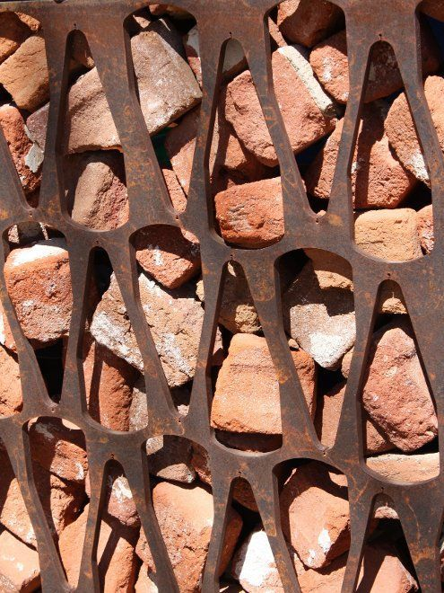 this is a huge twist on gabion. recycled broken brick, cor-ten patterned retaining screen.: