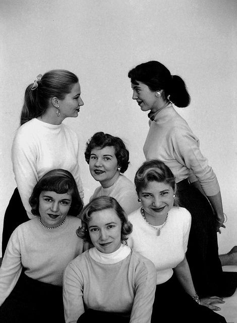 A portrait of six 1950s ladies sporting cute hairstyles and classic sweater and pencil skirt combos.