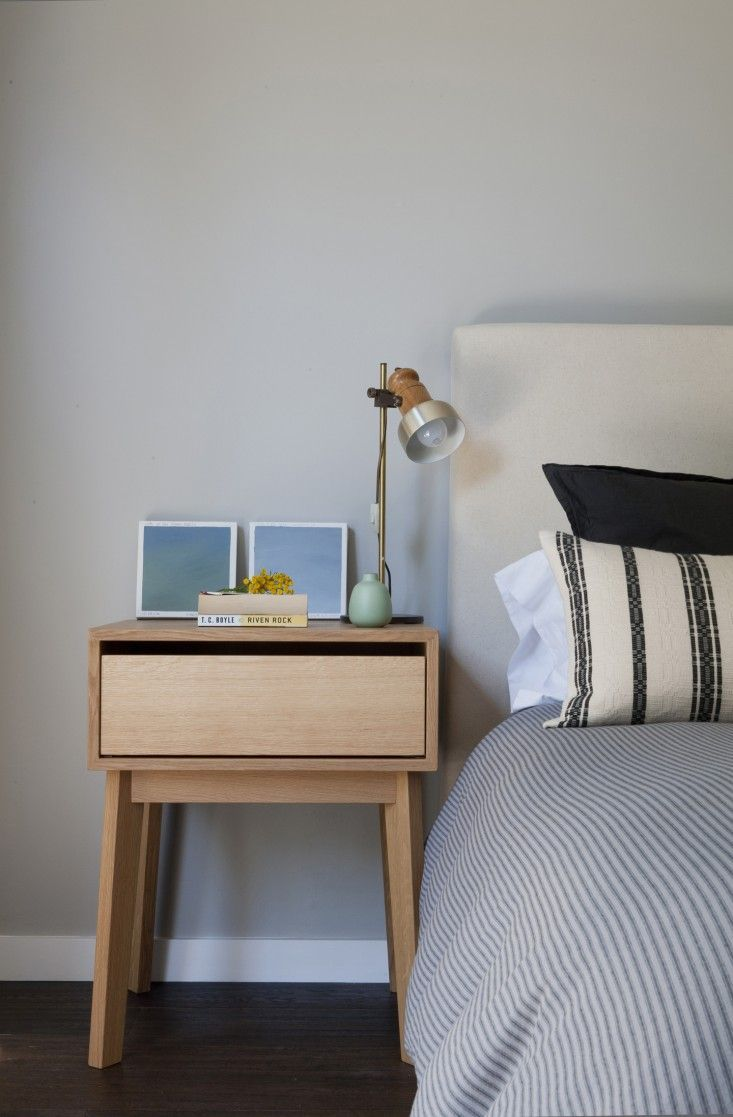 Fabric linen headboard with striped sheets and Hedge House bedside table in Venice apartment by SIMO Design | Remodelista