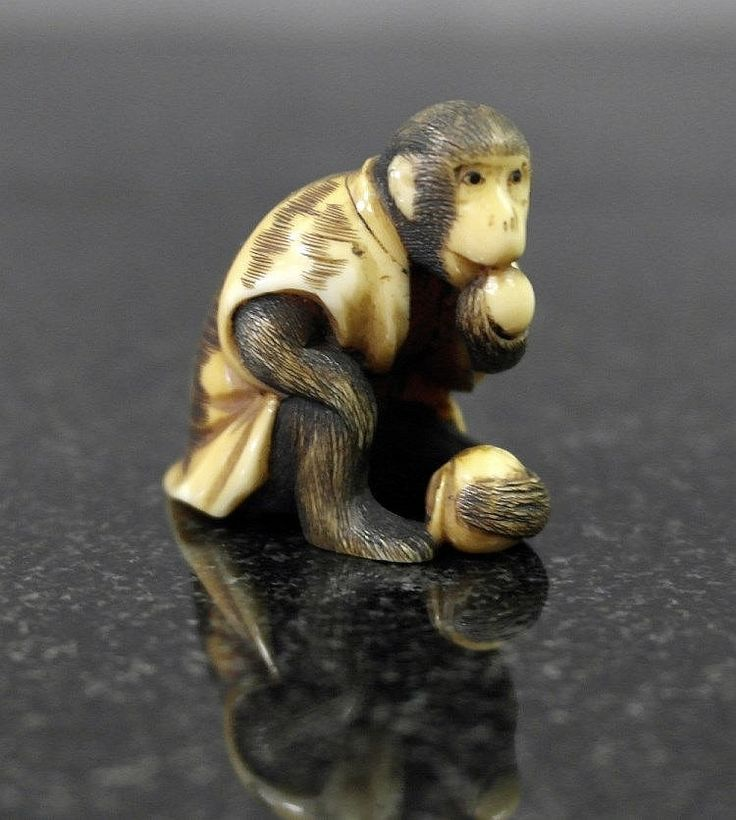 A Japanese ivory netsuke Edo period In the shape of a monkey eating fruit. H 2.5 cm (1.5'')