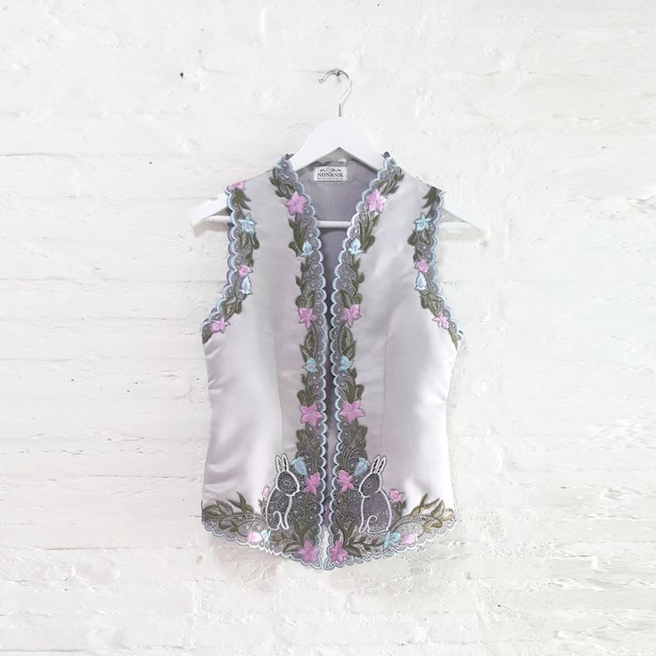 Lulu Rabbit 007  IDR 795.000  Open for Pre-Order  Estimated Work Days : 7 – 10 working days  Lulu Rabbit Hand Embroidery Contemporary Kebaya Vest  Length of Kebaya : (Front) approx. 70 cm / (Side) approx. 56 cm  Material used : Thick Dove Satin / Hand Embroidery  Free Size (Bust fit to 82 – 94 cm)  *Note: No button added on vest at the front