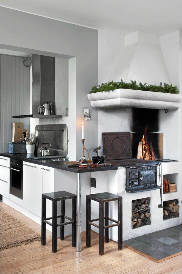 Gorgeous open flame fireplace in this white cottage kitchen.