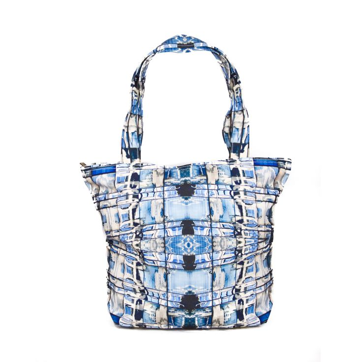 Glass walls  Stride with confidence with this striking pattern comprised of the melodious colors of blue and white. This easily parable tote bag perfectly translates to that of the skyscrapers of the concrete jungle known as New York. Jean Michel's signature pattern created from the reflections of buildings creates a salient look that works together to create a dashing first impression.