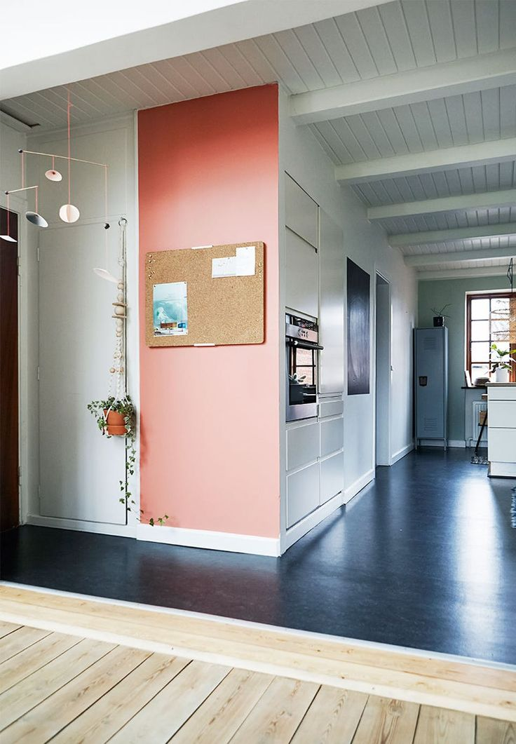 What a lovely open kitchen! The black linoleum floor is a cool and hard contrast to the clean white kitchen. The rosa wall with bulletin board is a wonderful detail and a colour splash to the neat room.
