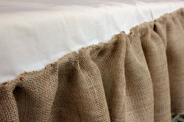 I pinned the burlap ribbon to each end and to the middle of the existing bed skirt. I pinched and pinned it all down. Then I sewed it right on top of the bedskirt. I used an entire roll for each side and half a roll for the end.
