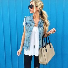 Denim vest with white tee, black pants, and long necklace.
