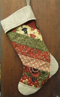 """by The Woolen Needle 10"""" X 18"""" - This fun and easy stocking goes together quickly. If you want to make it even faster, simply use a favorite fat quarter for the front instead of the pieced strips. Easy to personalize with a name on the top cuff. Pattern Only - $9 Kit Only - $20 (kit does not include pattern)"""