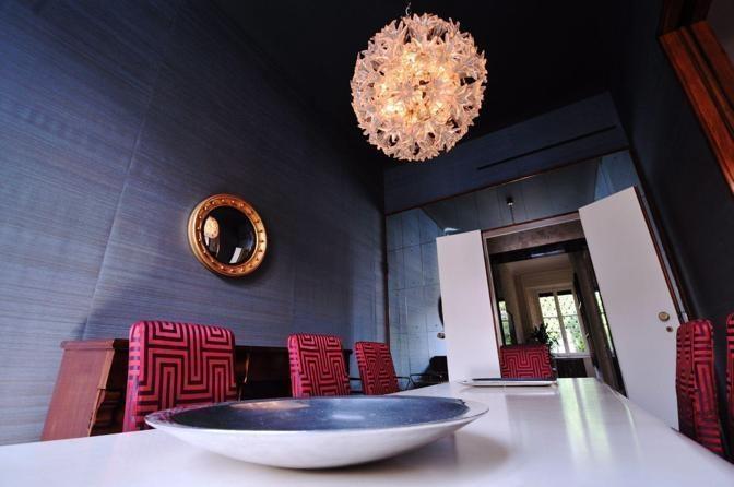 Antico e moderno si guardano negli occhi anche in sala da pranzo, dove le luci del lampadario Esprit di Venini (anni 60) rimbalzano sulla superficie convessa e deformante di uno specchio proveniente dall'allestimento di una mostra milanese: «Tiziano. Donna allo specchio».