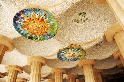 """Parte superior del """"Porche de la Plaza de la naturaleza"""". 86 columnas sostienen una gran plaza de arena. Ninguna columna está en ángulo recto respecto del suelo. La parte superior está recubierta de mosaico blanco y medallones muy coloridos."""