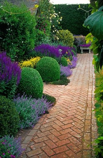 Pretty herringbone brick path, chunky box balls with an interesting stone bench as a focal point to draw you down to that end of the garden.