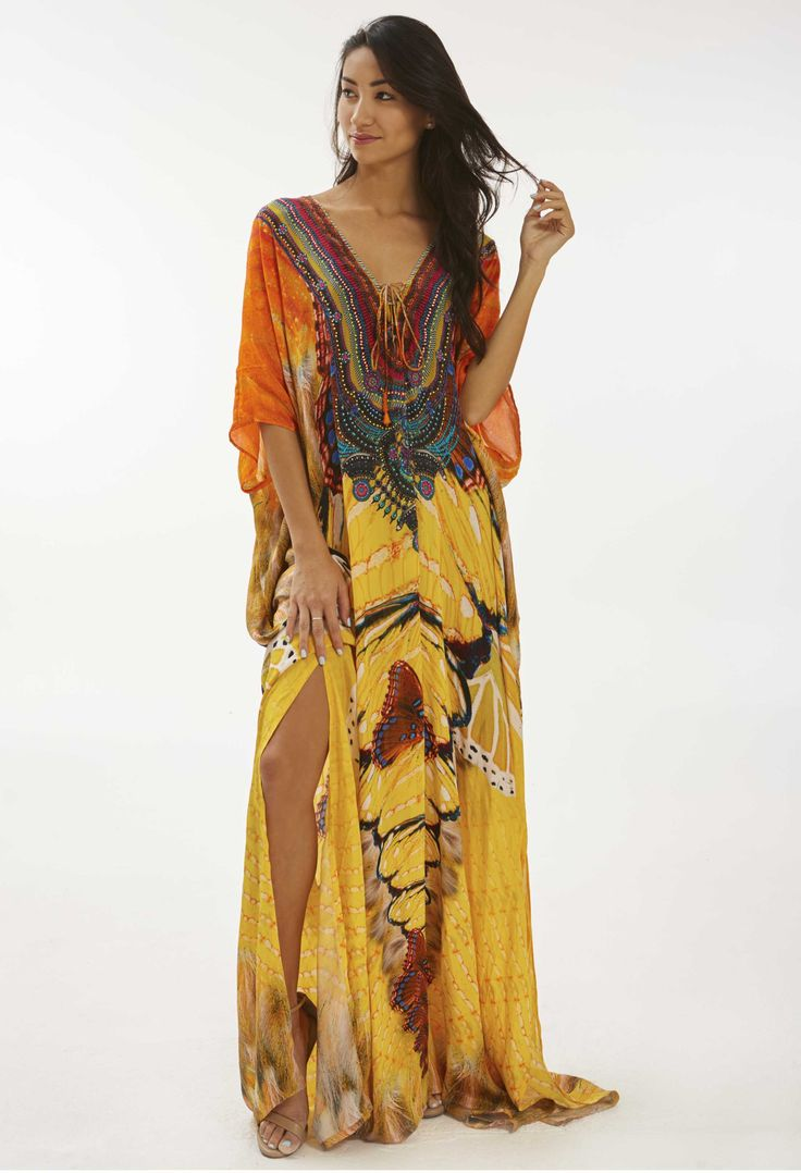 This brightly colored kaftan has discrete slits down each side, giving it the perfect touch of leg for a poolside dinner or tropical excursion in the Caribbean. Colorful crystal embellishments adorn t
