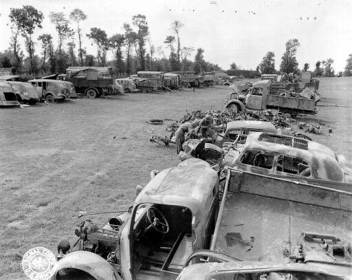 -Captured German Armour and Equipment dump in Normandy- Two GI's are looking at a Citroën traction 4c.