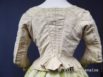 Back view of 1780/95 Camisole in ribbed & striped silk taffeta in shades of cream. Back cut diamond, angled sleeves finished in stove pipe and two buttons on cuffs. Closing on the front by pinning, sandwiched by a body/lining of linen lined in cream with green silk ribbon ties. Silk lining of faded pale pink.. Pet en l'aire or cacaraco back has two self covered buttons highlighting the already high waist. Off-white linen interior lining. Buttons are rare on a caraco/pet en l'aire!