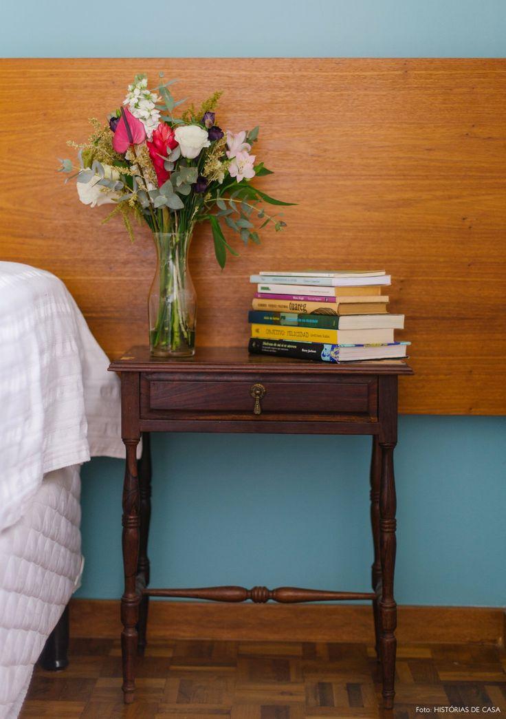 Parede azul, cabeceira de madeira e criado mudo antigo.