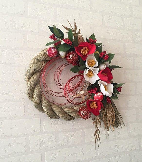 ご覧頂きありがとうございます。こちらは、アーティフィシャルフラワーを使用しましたお正月飾りです。紅白の椿と千両で作成したシンプルですが華やかなしめ飾りです。お正月は紅白に飾りたい!と言う方にオススメの作品です。水引で手作りしたオーナメントとちりめんボールで可愛らしく個性を出しました。アーティフィシャルフラワーですので雨が直接かからない場所であれば屋外使用可能で何年もお使い頂けます。和室に飾って頂いてもステキです。アーティフィシャルフラワーは全て東京堂の花を使用しています。サイズ→約35cm×30cm #しめ飾り#しめ縄#松ちりめん#水引#お正月飾り#千両#椿#和室飾り#しめ縄リース