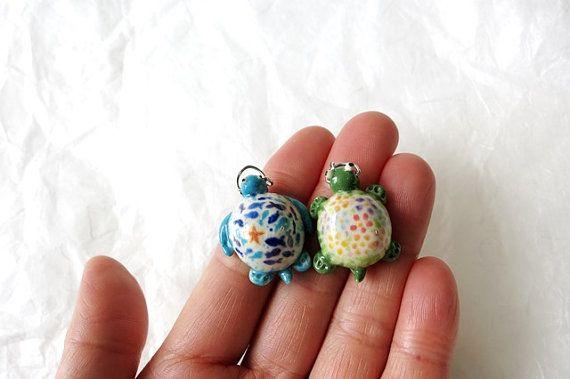 Die Schildkröte und Schildkröte Halsketten mit schönen Szenen auf ihren Schalen! Die grüne Schildkröte ist in der Blumenwiese, während die blaue Schildkröte im Ozean schwimmt. Die Charms sind von mir handgefertigt mit Porzellan Ton, zweimal mit Unterglasur-hohe Feuer Glasur gebrannt. Sowohl Reize werden über 1(2.54cm) in der Länge, 3/8(0.95cm) in der Höhe. * Wenn Sie eine andere Kettenlänge bevorzugen würde, lass es mich wissen. * Der Porzellan-Charme ist haltbar, aber zerbrechlich, bit...