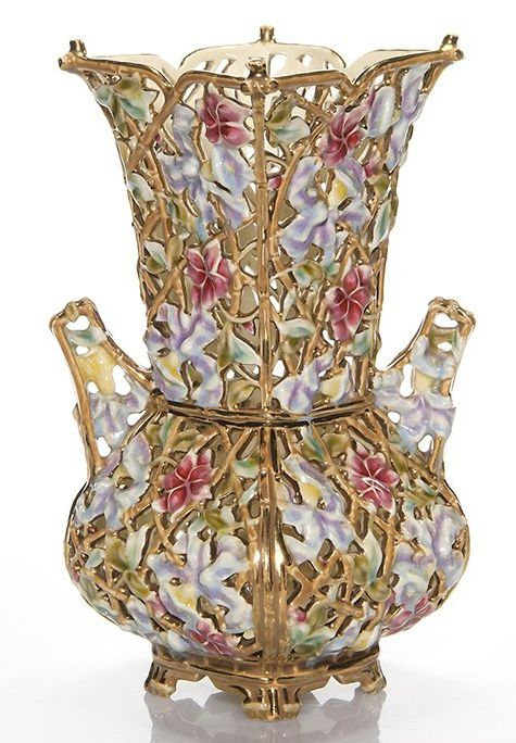 "Zsolnay Pecs vase, fully reticulated, imitating natural latticed vines supporting lavender blue orchids and pink flowers. An enhancement of shiny gold heightens to a splendid glow. Impressed ""Made in Austria-Hungaria, Zsolnay Pecs, 3683-15"" and stamped ""Made in Austria-Hungaria"" with the 5 Towers logo. A monogram in gold possibly the artist. Height 10 inches. 14/L450U"