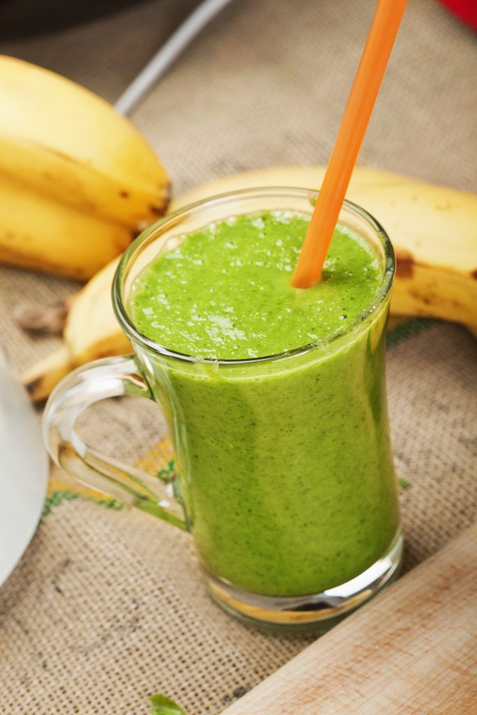 Fresh Green smoothie in glass cup with few bananas in background; Adobe RGB color space;see other similar images: