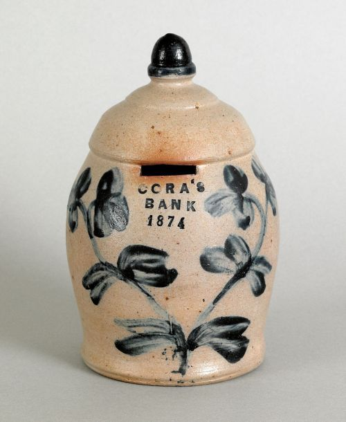 "Fine stoneware bank dated 1874, attributed to Peter Hermann, Baltimore, inscribed Cora's Bank, 8"" h. Sold for $20,145"