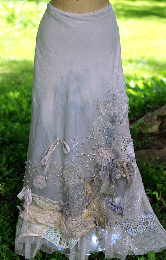 Romantic vintage linen blend maxi skirt, with lots of intricate details-old laces and distressed cotton flounces draped at front, with torn silk blooms, shiny clear seed beads like water drops. The bottom edge is trimmed with dusty cream tulle with tiny silver dots, and at front with vintage lace pieces. Fastens at side with zip and button, the material is linen/viscose blend, bias cut. The skirt has satin lining. Comfortable to wear and drapes well. For sz L ( uk sz 14 , eur 42, us 12 )…