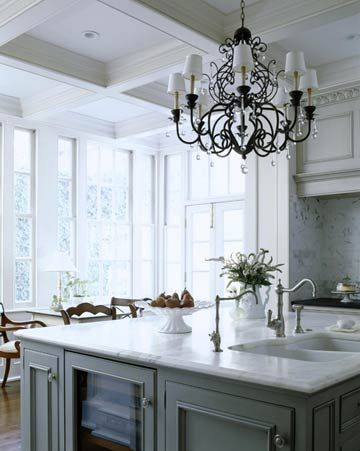 I love the wrought iron chandelier, the huge windows enclosing the eating area, and the cool color scheme.