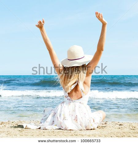 Portrait of young woman on the beach near the sea sitting with hands up wearing sophistical dress and hat. Photo from behind - stock photo