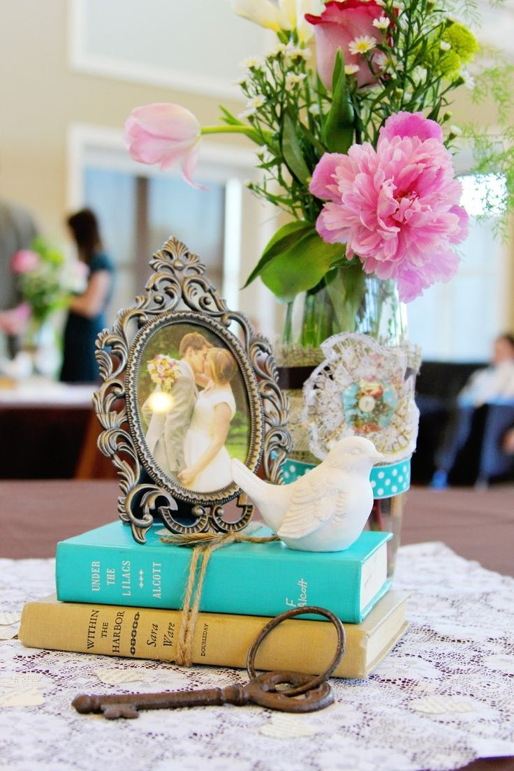 Vintage themed centerpiece with books and framed photo of the couple #wedding #vintage #vintagewedding #centerpiece #tablescape