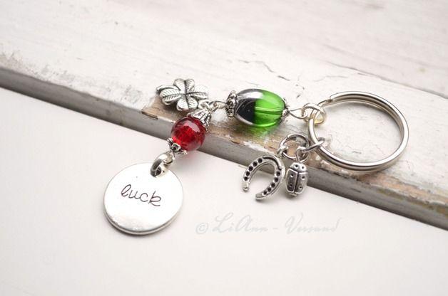 Super niedlicher, silberner Schlüsselanhänger aus einem Schlüsselring aus Metall, an dem ein langer Anhänger aus einer grün-silbernen Glasperle und einer roten Crush-Perle aus Glas angebracht ist....