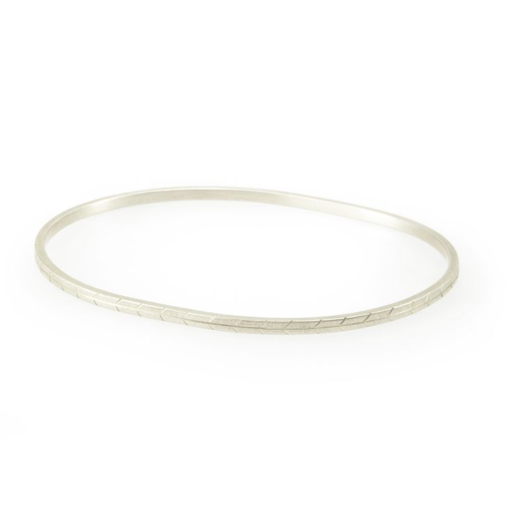 An oval shaped bangle designed to echo the shape of the wrist with a grassveld inspired pattern. The grassveld bangle is delicate when worn alone but is also a the perfect addition to a group of plain oval bangles.