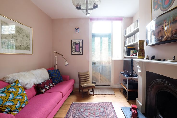 The living room is painted in Farrow and Ball's Setting Plaster. Nisha's mum made the Dutch wax print cushions herself. The pink sofa is John Lewis. The small chair was found at a Sue Ryder charity shop in Lee. The poole vase is from Granby Antiques in Clevedon. Everlasting ice cream is by Pippa Choy.                                         The sheepskin rug on sofa is from Forest and Co. The floor lamp was found on the street. Purple and black 1970s abstract picture is by Bob Lawrie. The…