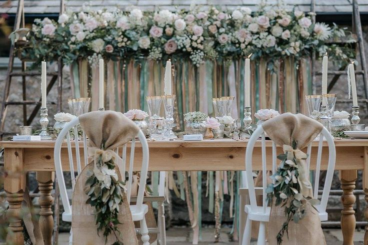 Intimate wedding breakfast with white chairs dressed with hessian sashes