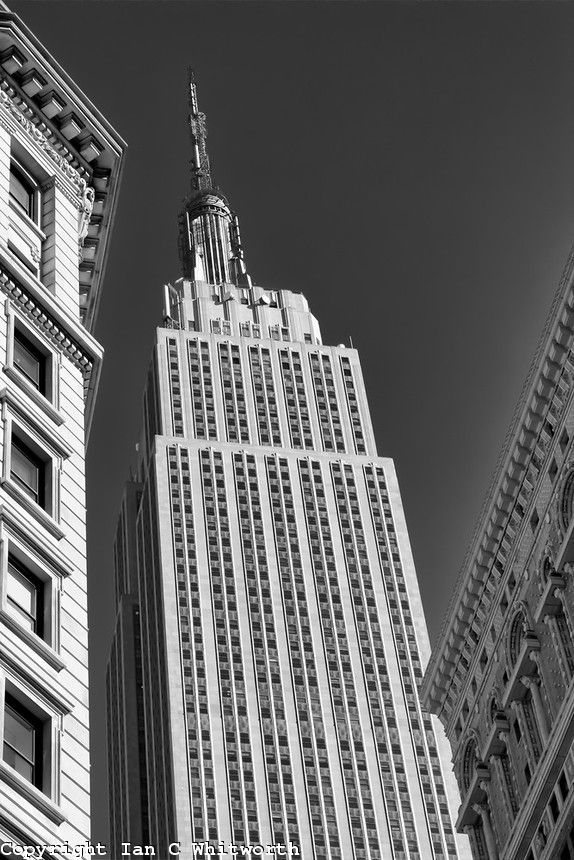 Looking up between the buildings at the Empire State Building in NYC in black and white.